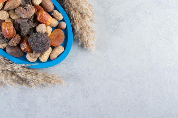 Assortiment van smakelijke gedroogde vruchten en noten op stenen achtergrond.