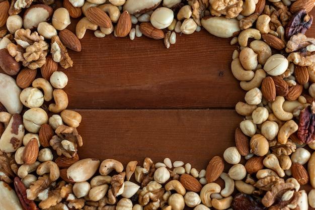 Assortiment van smakelijke noten op houten achtergrond. kader. bovenaanzicht. vrije ruimte voor uw tekst.