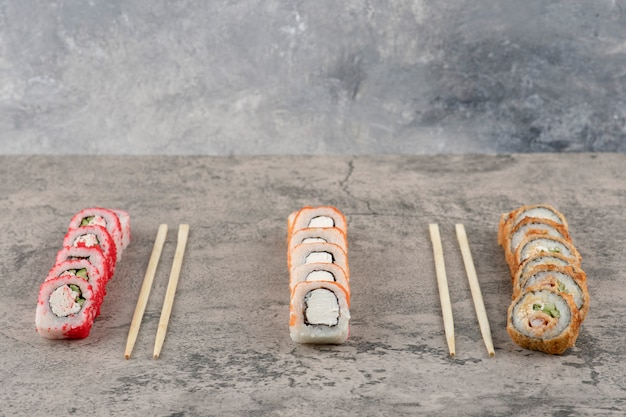 Assortiment van smakelijke sushibroodjes die op marmeren achtergrond worden geplaatst