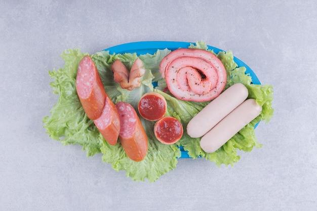 Assortiment van smakelijke worstjes op blauw bord.