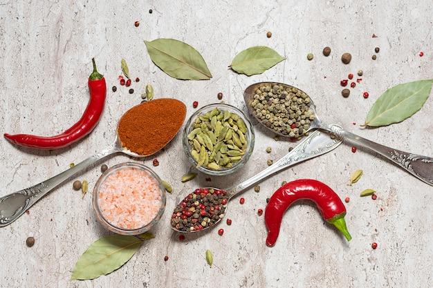 Assortiment van specerijen, kruiden en himalaya zout op licht marmeren tafelblad bekijken.