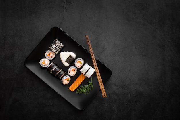 Assortiment van sushi op zwarte rechthoekige plaat met kopie ruimte