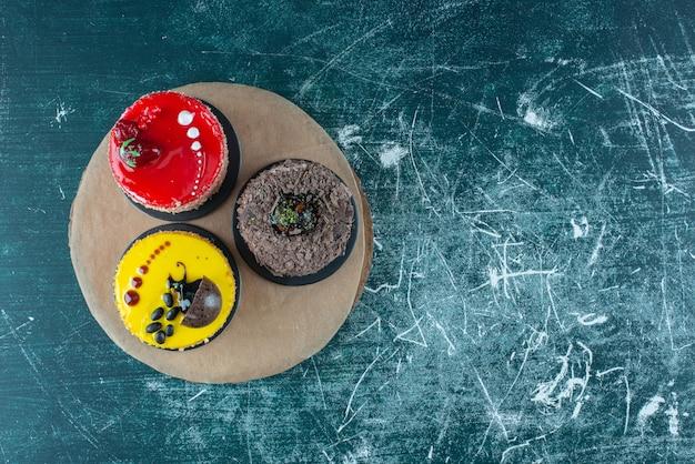 Assortiment van taarten op een houten bord op blauw.