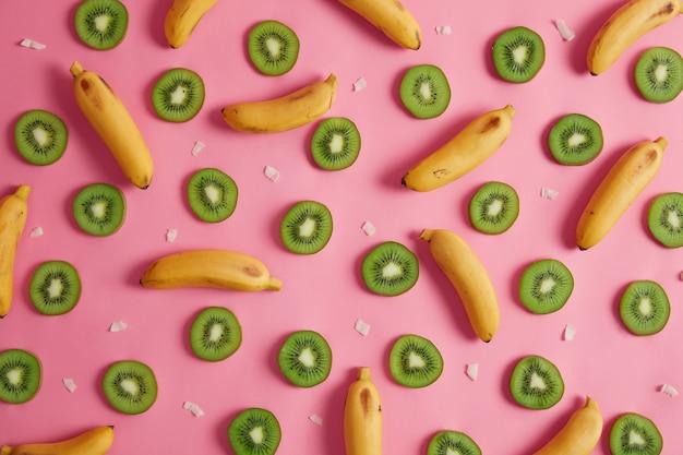 Assortiment van tropisch fruit. snijd plakjes kiwi met zwarte eetbare zaden, hele gele bananen en kokosvlokken op een roze achtergrond. ingrediënten voor het maken van multivitaminesap, smoothie of fruitsalade