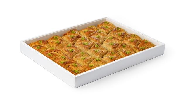 Assortiment van turks baklava-dessert in een witte doos die op witte achtergrond wordt geïsoleerd