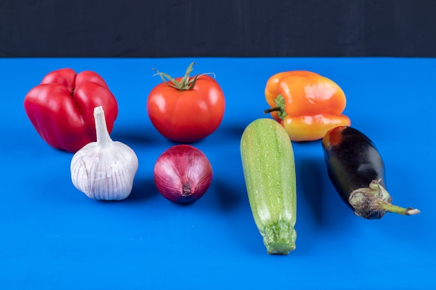 Assortiment van veel verse rijpe groenten op blauwe ondergrond