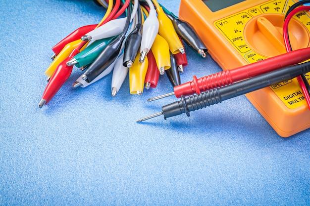 Assortiment van veelkleurige clipkabels en digitale multimeter op blauw oppervlak