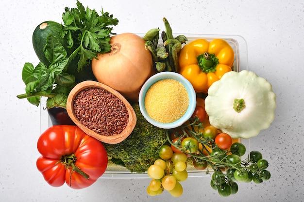 Assortiment van vers fruit en biologische veelkleurige regenbooggroenten op grijze betonnen ondergrond. eten koken en gezonde schone voedselachtergrond en mock-up.