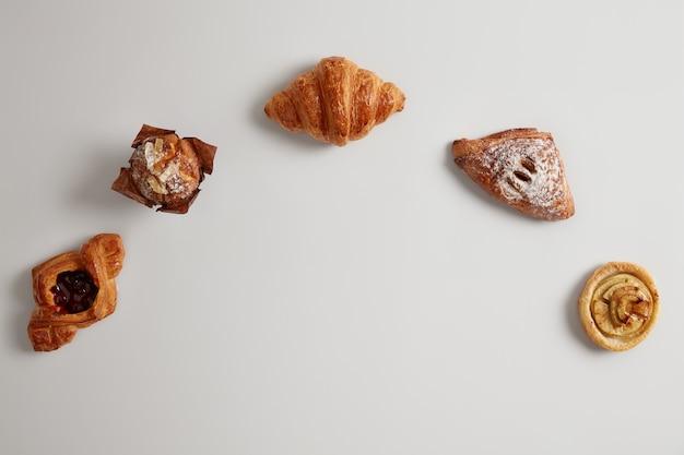 Assortiment van vers gebakken zoete bakkerijproducten. broodjes, croissant, broodje, muffin die in halve cirkel tegen witte achtergrond wordt geschikt. kopieer ruimte in het midden van de opname. bladerdeeg. bakkerij levensmiddel