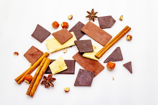 Assortiment van verschillende chocoladetypes, specerijen en hazelnoten boven wit