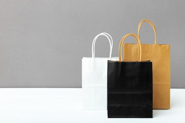 Assortiment van verschillende colourcraft papieren tassen. het winkelen doet document pakketten in zakken op witte lijst grijze achtergrond met exemplaarruimte. winkelen, verkoop, bezorgservice.