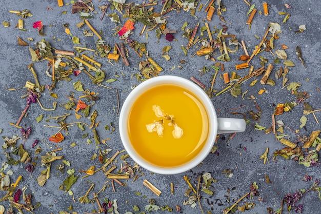 Assortiment van verschillende droge theebladeren en twee kopjes groene thee. biologische kruiden, groene aziatische thee met droge bloemblaadjes voor de theeceremonie. plat lag, kopieer ruimte voor tekst