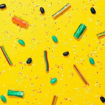 Assortiment van verschillende gekleurde snoepjes op gele achtergrond