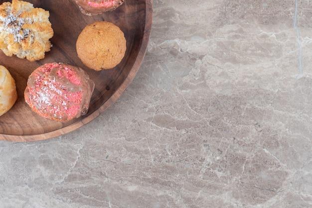 Assortiment van verschillende koekjes op een houten dienblad op marmeren ondergrond