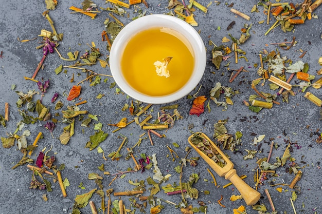 Assortiment van verschillende kwaliteit droge theebladeren in houten lepel en kopje groene thee. biologische kruiden, groene en zwarte thee met droge bloemblaadjes voor de theeceremonie.