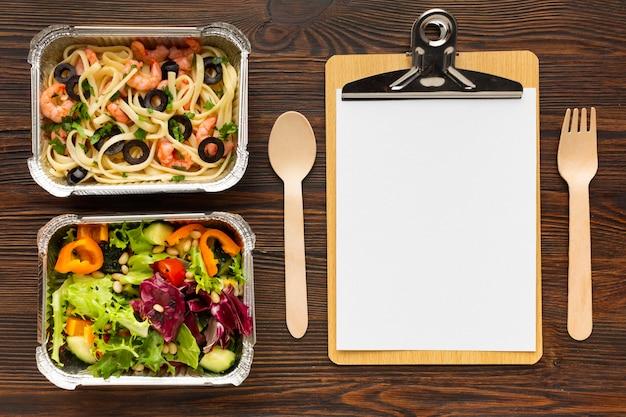Assortiment van verschillende maaltijden met leeg klembord