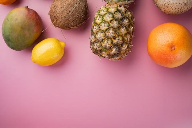 Assortiment van verschillende soorten fruit, op roze getextureerde zomerachtergrond, bovenaanzicht plat gelegd, met kopieerruimte voor tekst