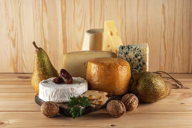 Assortiment van verschillende soorten kaas op houten tafel.