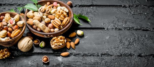 Assortiment van verschillende soorten noten in kommen op zwarte rustieke tafel.