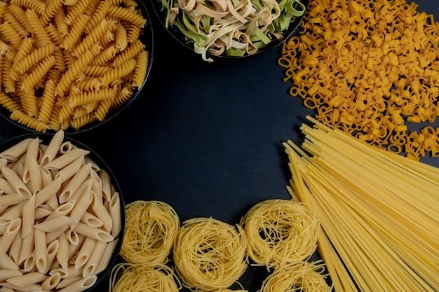 Assortiment van verschillende soorten pasta droog op zwarte achtergrond.