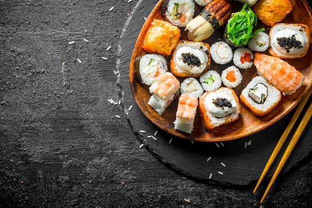 Assortiment van verschillende sushi rolt op een bord met stokjes.