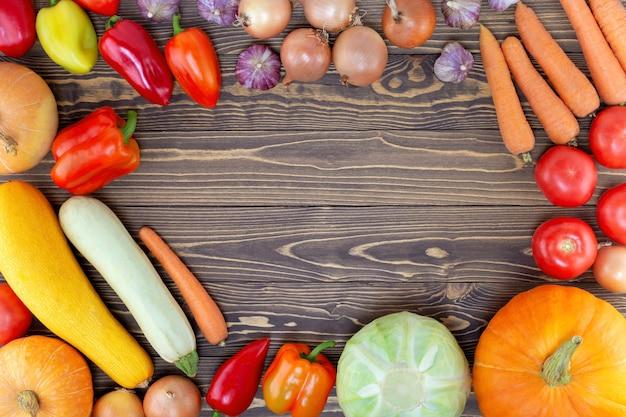 Assortiment van verse biologische groenten op houten achtergrond. bovenaanzicht met kopie ruimte.