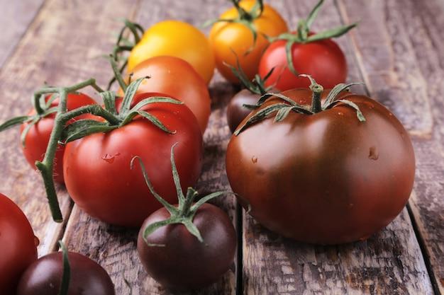 Assortiment van verse biologische kleurrijke tomaten op houten oppervlak.