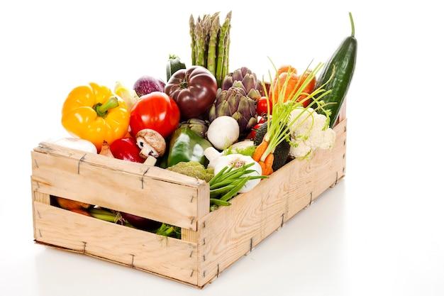 Assortiment van verse groenten in een krat op witte achtergrond
