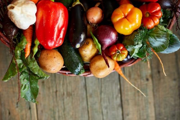 Assortiment van verse groenten in een mand, bio-gezond, biologisch voedsel op houten achtergrond, landelijke marktstijl, tuinproducten, vegetarisch dieetvoedsel, schoon eten.