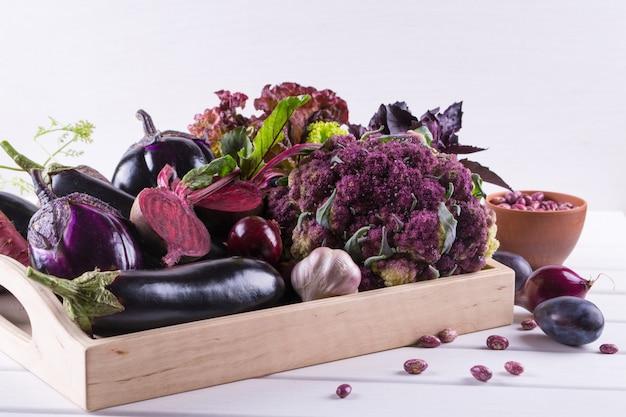 Assortiment van verse rauwe paarse homegrown groenten op donkere houten tafel. bloemkool, aubergine, bieten, wortelen, aardappelen, pruimen, basilicum, uien, knoflook, bonen, sla.