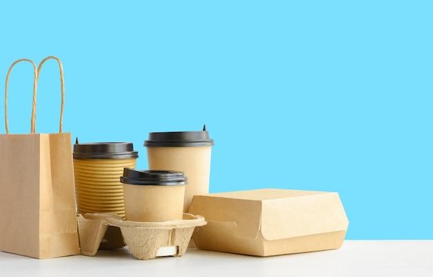 Assortiment van voedselbezorgingscontainers op tafel op blauwe muurachtergrondkopieerruimte