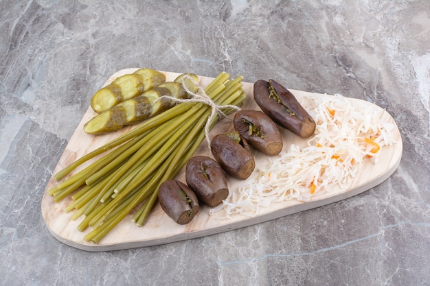 Assortiment van zelfgemaakte augurken op een houten bord.