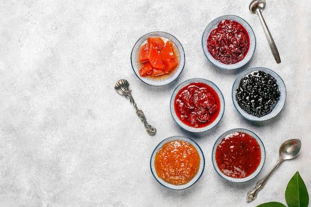 Assortiment van zoete jam en seizoensfruit en bessen