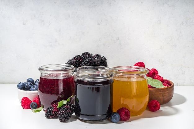 Assortiment van zomer seizoensgebonden bessen en fruit jam in kleine potten, zelfgemaakte conserveringsconcept, marmelade of confitures met verse bessen op witte achtergrond kopie ruimte
