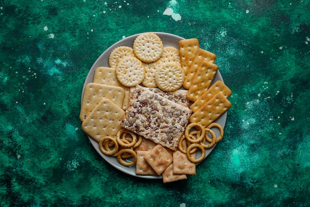 Assortiment van zoute crackers geschoten vanaf de bovenkant op kleurrijk met kopie. zoute feest snacks mix