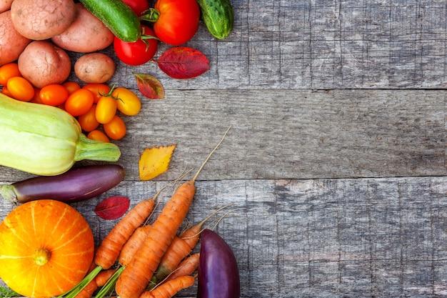Assortiment verschillende verse biologische groenten op landelijke stijl houten achtergrond. gezonde voeding veganistisch vegetarisch dieet concept. lokale tuin produceert schoon voedsel. frame bovenaanzicht plat lag kopieerruimte
