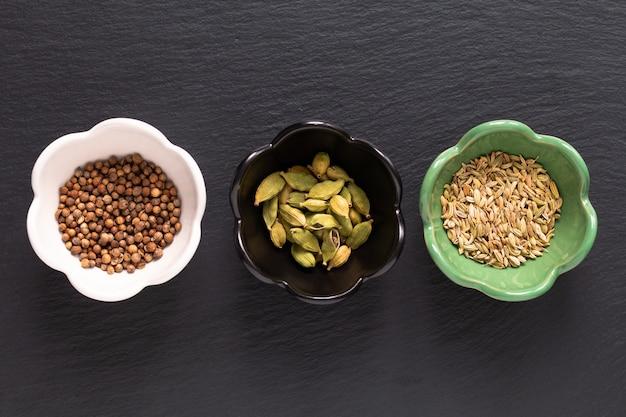 Assortiment voedingsmiddelenconcept oosterse kruiden kardemompeulen, korianderzaad, venkel op zwarte leisteen