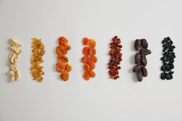 Assortiment zeer voedzame gedroogde vruchten, rijk aan vitamines en mineralen. gedroogde appel, rozijnen, abrikoos, physalis, berberisfamilie en datums op witte achtergrond. een gezonde snack kan aan pap worden toegevoegd