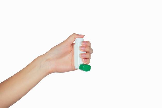 Astma-inhalator in de hand op wit isolaat