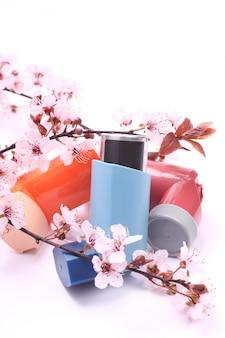 Astma-inhalatoren met bloeiende boomtakken over wit