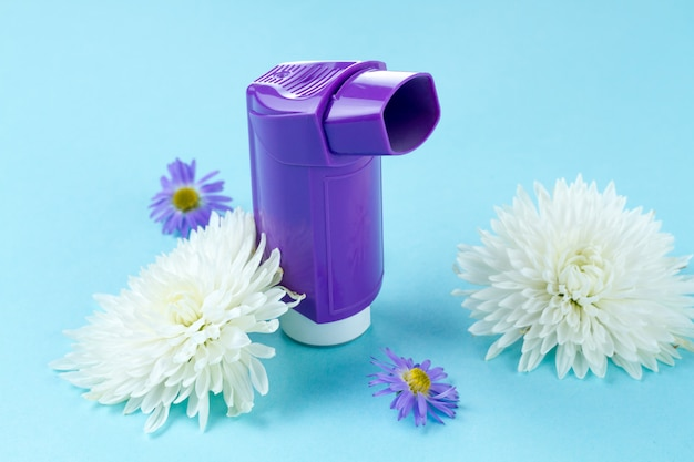 Astma-inhalers en bloemen op blauw
