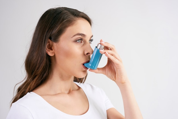 Astmatische vrouw die een astma-inhalator gebruikt tijdens astma-aanvallen