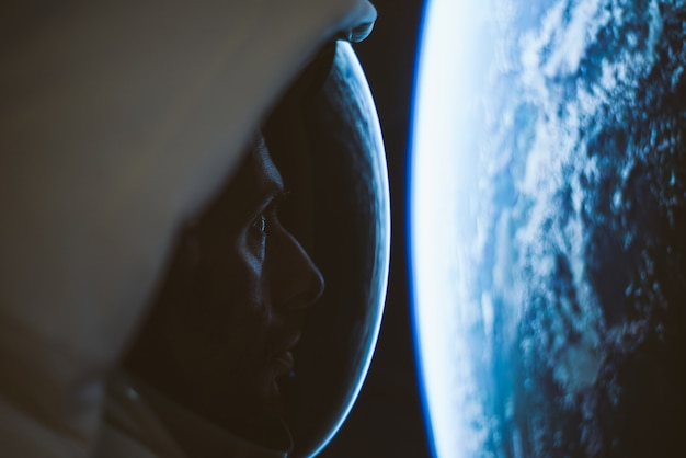 Astronaut kijkt vanuit het raam van zijn capsule naar de verre ruimte, de melkweg en de planeten. concept over wetenschap en ruimteverkenning