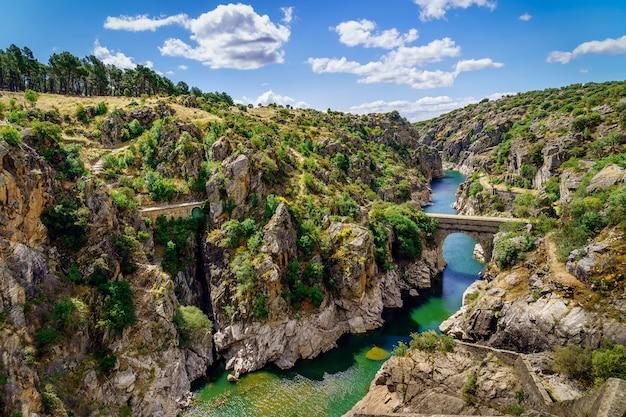 Atazar madrid reservoir canyon met rivier van water en stenen brug over de rivier. spanje,
