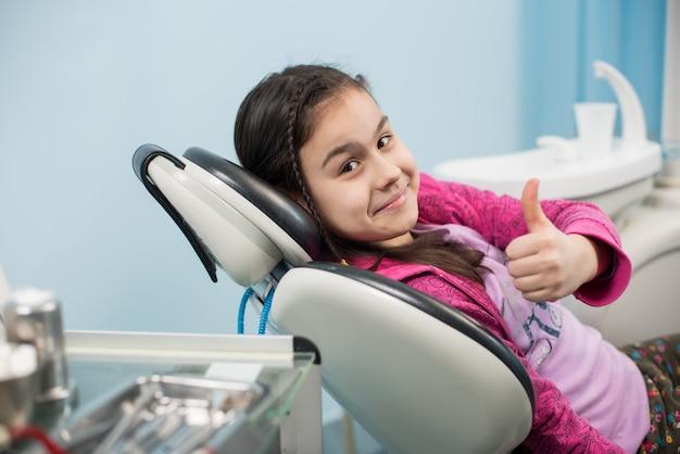 Atientmeisje die duimen tonen op tandkantoor
