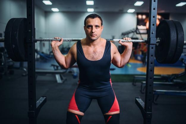 Atleet bereidt zich voor om squats met barbell te maken