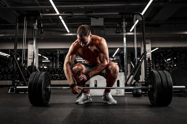 Atleet, bodybuilder oefening met een barbell, atleet bereidt de barbell voor op oefening, mooi lichaam, gezonde levensstijl.