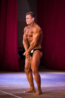 Atleet bodybuilder toont buikspieren en borst bij wedstrijden