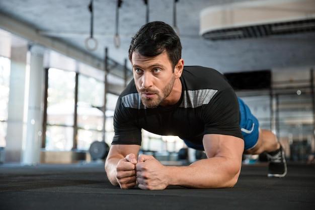 Atleet die blauwe korte broek en zwart t-shirt draagt die statische oefening maakt