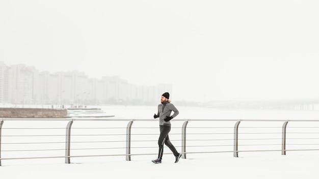 Atleet die buiten in de sneeuw loopt